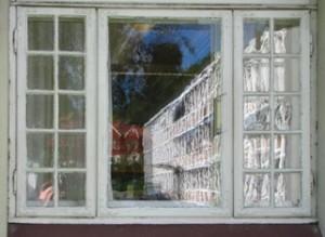 Kommunehuset speglar seg i dei gamle vindua på biblioteket (Foto: Siri Johannesen)
